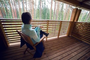 girl in a blue sweater sitting on  wooden chair and drinking tea