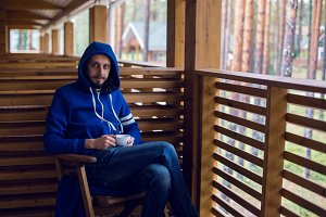 guy in a blue jacket with  hood draped on his head sitting   chair