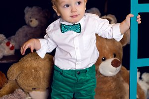 little child standing on the floor near the Christmas bears in the white shirt and green pants