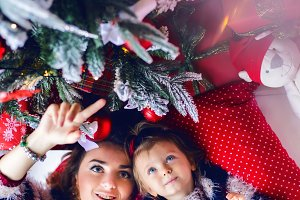 mother and daughter lying under the Christmas tree