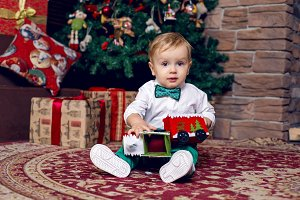 little child sitting on the floor near the Christmas tree in the white shirt