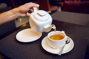 man pours tea from a white teapot in   Cup