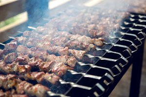 large number of preparing kebabs on the grill