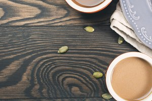 Wooden background with cups of coffee