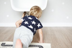 Indoor shot of adorable little boy dressed in sleeping suit with stars, lying on carpet in children's room. Rear shot of Caucasian infant having fun and playing on his own on wooden floor in bedroom