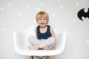 Portrait of playful toddler with fair hair wearing pajamas, sitting on chair cross-legged, looking at camera, laughing, mouth wide open, showing his white teeth, against blank wall win Batman logo