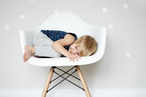 Happy carefree childhood. Sweet Caucasian infant rolling himself up in white designer chair, hiding from his friends while playing hide-and-seek. Cute baby boy having fun indoors. Visual effects