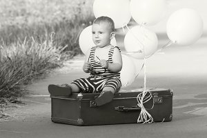 small boy sits in an old suitcase