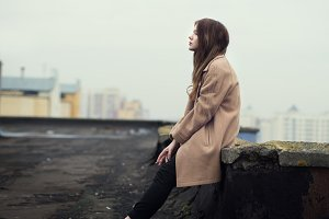 girl in a coat on the roof