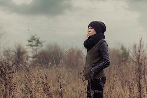 Girl in a field on a cloudy day