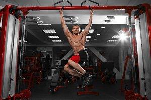 Muscular man doing pulling up on horizontal bar.