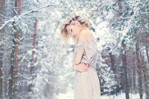blonde in dress among winter forest