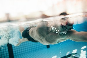 Male athlete swimming in pool.