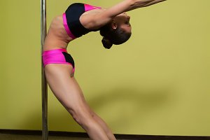 Woman is practicing pole dance