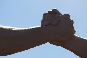 Friendly handshake of two unrecognizable muscular white men on blue sky background. Shaking of male arms outdoor. Two strong men having firm handshake outside. Teamwork and friendship. Close-up