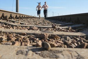 Two men are running between rails on railroad tracks. Sprinting runner guys jogging on railway sleepers. Legs of sport athletes training outdoor at summer. Active healthy lifestyle outside. Close-up