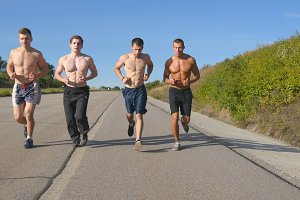 Group of runners men jogging at highway. Male sport athletes training outdoor at summer. Young strong muscular guys exercising on rural road during workout together. Active healthy lifestyle. Close-up