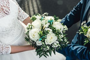 White roses in hands of the bride and groom. Image for wedding blogs, greeting cards