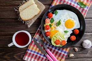 Fried eggs in pan with tomato, bread, pepper and parsley on wooden background