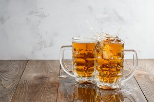Two Oktoberfest beers splash on a wooden table