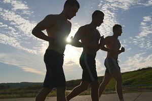 Silhouette of strong men jogging in the country road at sunset time. Group of male jogger training for marathon run. Athletes exercising and running against blue sky. Healthy active sport lifestyle.