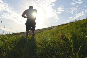 Young man running over green hill over blue sky background. Male athlete is jogging in nature at sunset. Sports runner jogging uphill outdoor at sunrise with flare. Cross-country training. Lifestyle