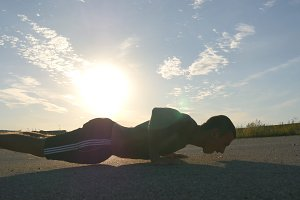 Young strong man making pushups outdoor. Fit muscular male fitness guy warming up before running. Athlete training push-up on country road at sunset. Healthy active workout lifestyle. Close-up