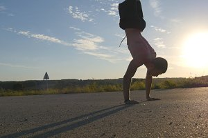 Young strong man showing impressive strength, doing a handstand outdoor. Fit muscular male fitness guy doing stunts on country road at sunset. Athlete training performs a handstand at muscle. Workout
