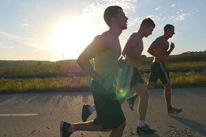 Three strong men jogging in the country road at sunset time. Group of male jogger training for marathon run. Athletes exercising and running against blue sky. Healthy active sport lifestyle