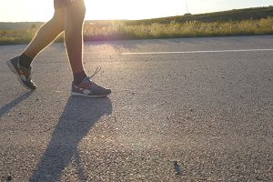 Male feet is walking on a rural road at sunset, close up. Young man is walking down an empty country road. Guy crossing a sunlit route. Legs of young boy move along the pathway. Highway in evening.