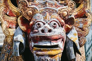 Close up view of colorful carved traditional demon guard statue in stone in Indonesia, Bali.