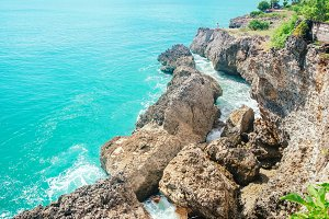 Scenic view from high mountain cliff on colorful blue Indian ocean water hitting rocks in Bali, Indonesia. Sea nature landscape