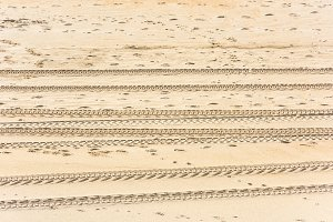 Traces of car tires on the sand