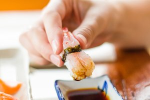 Hand dipping sushi on soya sauce