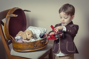Boy playing with old tin toys