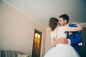 young bride and groom embracing in the background at home