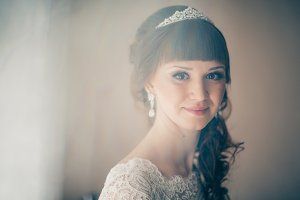 portrait of a young bride smiling and standing near  window