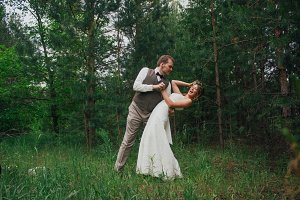 Bride and groom fooling around on the background of leaves forest