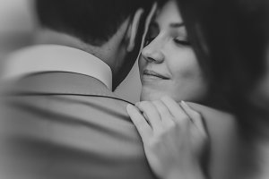 black and white photo of young happy bride embraces groom soft focus