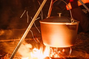 boiling pot over an open fire on a blurred background