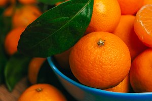 many fresh mandarin oranges in a blue bowl close-up