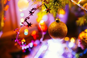 Golden ball on a background of green Christmas tree branches
