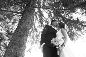 black white photography bride and groom on the background trees