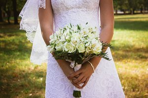 the bride holding a bouquet of multicolored roses