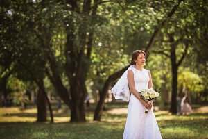 portrait of a young bride with  wedding bouquet on  park background