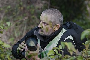 war photographer camouflaged in the vegetation