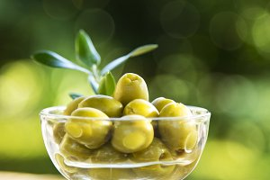 cup green olives with background