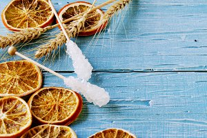 Dried orange slices and sugar sticks on blue wooden table