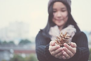 Girl holding pine cone