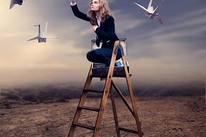 Woman on ladder with paper kites